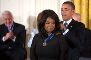 Oprah receiving a peace medal from President Obama